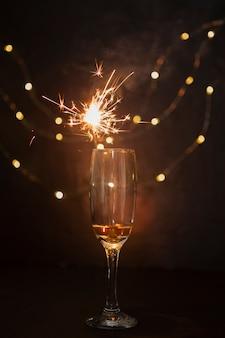 Disposizione con bicchiere di champagne e fuochi d'artificio