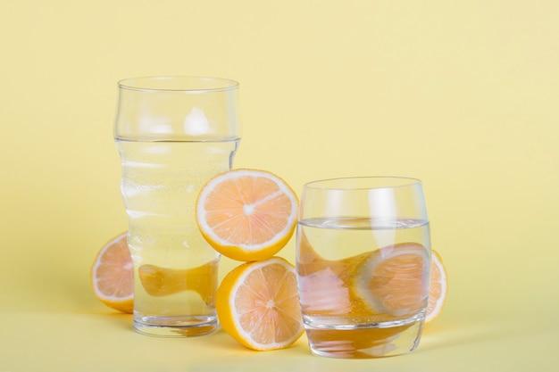 Disposizione con bicchieri d'acqua e limoni