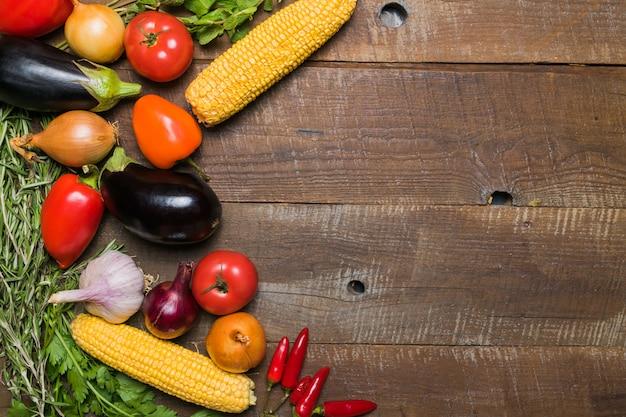 Disposizione con differenti verdure sulla vecchia tavola di legno con lo spazio della copia.