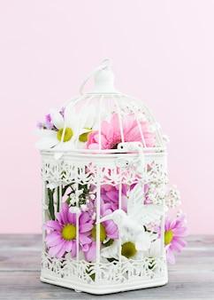 Disposizione con gabbia per uccelli piena di fiori