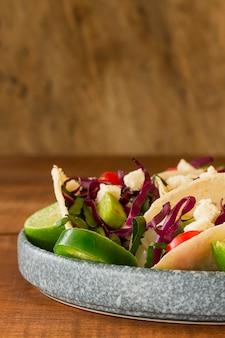 Disposizione con gustosi tacos sul piatto
