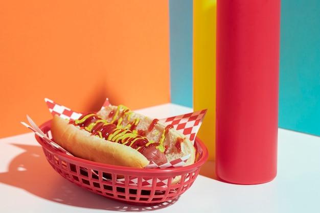 Disposizione con hot dog in cesto e bottiglie di salsa