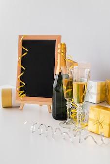 Disposizione con lavagna mock-up e champagne