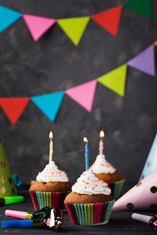 Disposizione con muffin e candele su fondo di legno