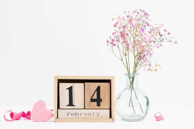 Disposizione con nastro rosa e vaso di fiori