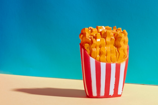 Disposizione con patatine fritte di plastica e sfondo blu