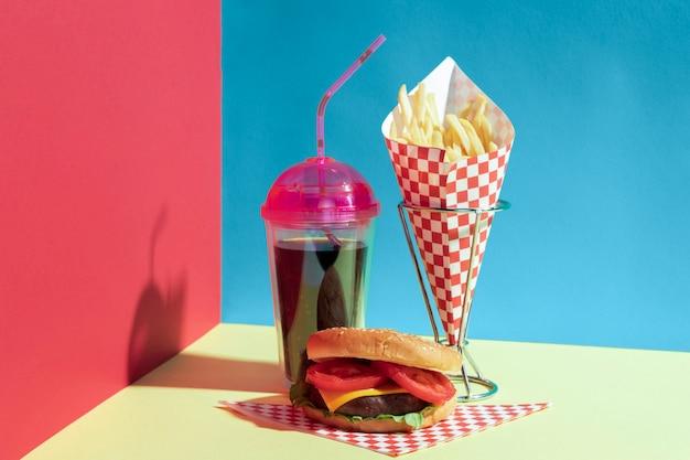 Disposizione con patatine fritte su supporto e tazza di succo