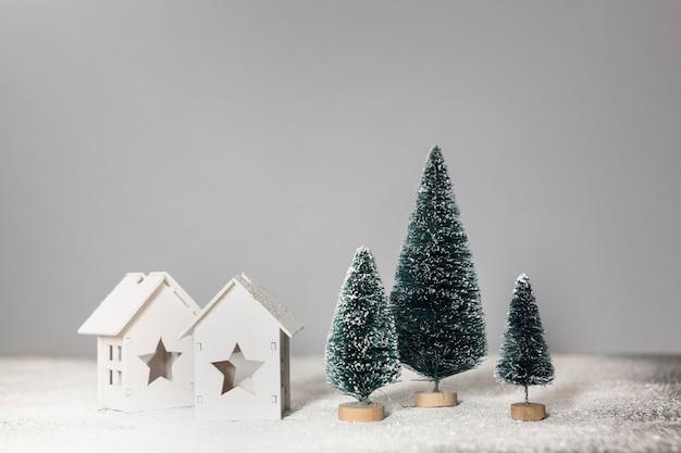 Disposizione con piccoli alberi di natale e case