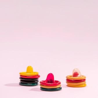 Disposizione con preservativi su sfondo rosa