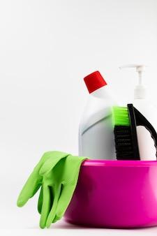 Disposizione con prodotti per la pulizia in bacinella rosa