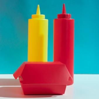 Disposizione con scatola rossa e bottiglie di salsa