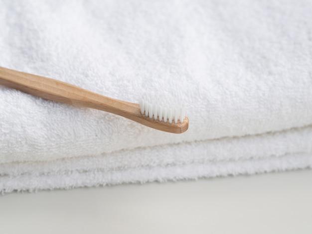 Disposizione con spazzolino da denti in legno e asciugamani