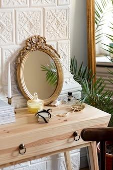 Disposizione con specchio e profumo sul tavolo di legno
