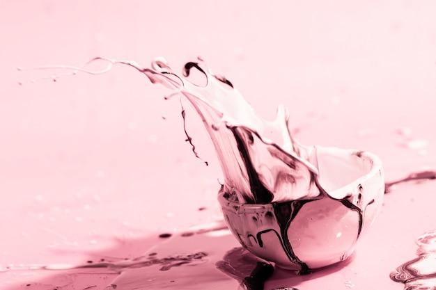 Disposizione con spruzzi di vernice rosa e tazza