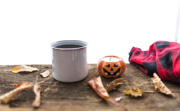 Disposizione con tazza e candela sul tavolo di legno