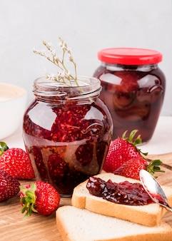 Disposizione con vasetti di marmellata di fragole