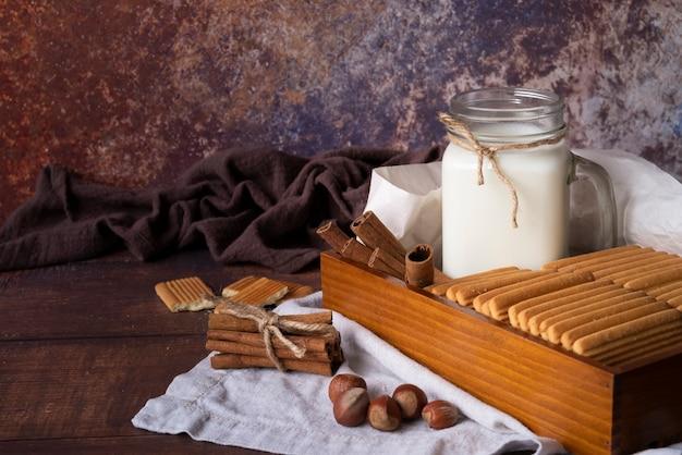 Disposizione con vasetto di latte e biscotti