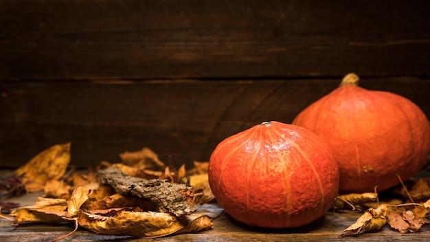 Disposizione con zucche e foglie su fondo in legno