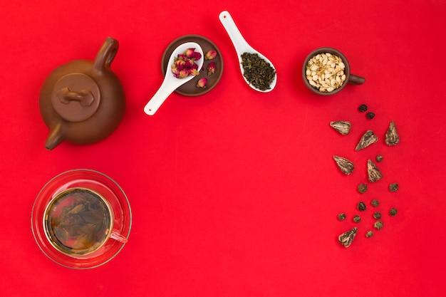 Disposizione cornice piatta con foglie di tè verde cinese, boccioli di rosa, fiori di gelsomino e una teiera di argilla. sfondo rosso