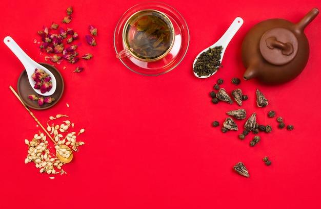 Disposizione cornice piatta con tè verde cinese, boccioli di rosa, fiori di gelsomino e foglie di tè secche. sfondo rosso copyspace