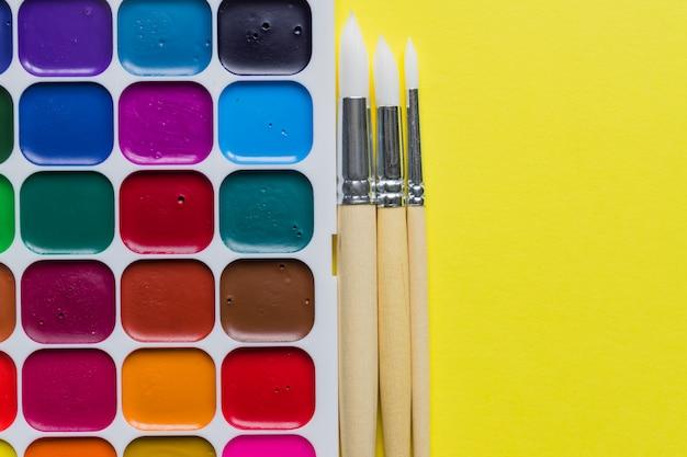 Disposizione creativa con la tavolozza dell'acquerello, pennelli su giallo