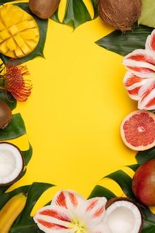 Disposizione creativa del piano con i frutti tropicali e le piante sul fondo giallo del copyspace