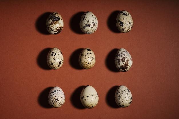 Disposizione creativa dell'uovo di quaglia sullo spazio marrone. modello di uova di quaglia.