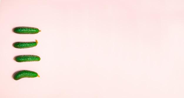 Disposizione creativa fatta del cetriolo sul rosa