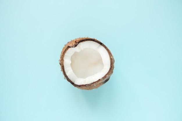 Disposizione creativa fatta di mezza noce di cocco matura sul blu