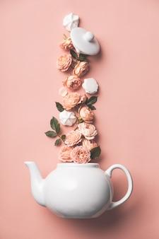 Disposizione creativa fatta di teiera bianca con rose arancioni e merengues su rosa