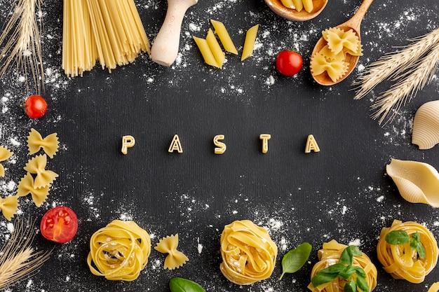 Disposizione cruda della pasta con la pasta di alfabeto su fondo nero
