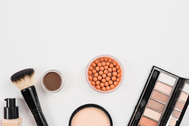 Disposizione da prodotti di bellezza cosmetici posa su sfondo bianco