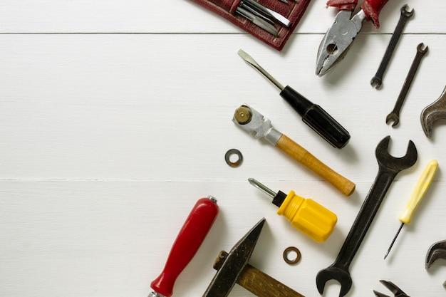 Disposizione degli strumenti di riparazione e costruzione su un fondo di legno bianco. spazio per il testo