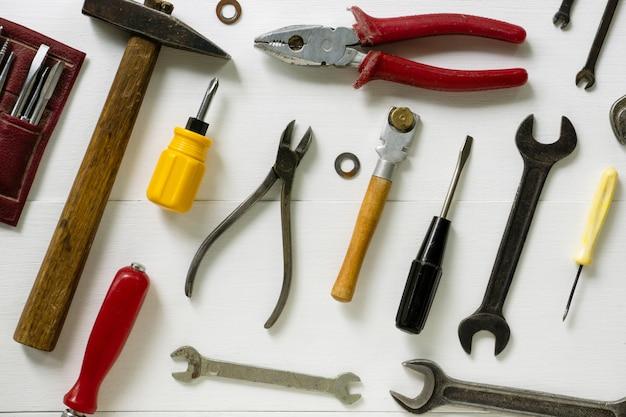 Disposizione degli strumenti di riparazione e costruzione su un fondo di legno bianco