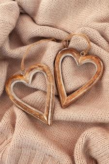 Disposizione dei cuori di legno sul maglione caldo. posa verticale piatta.