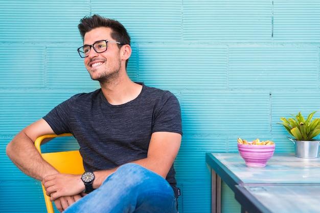 Disposizione dei posti a sedere felice del giovane in un ristorante