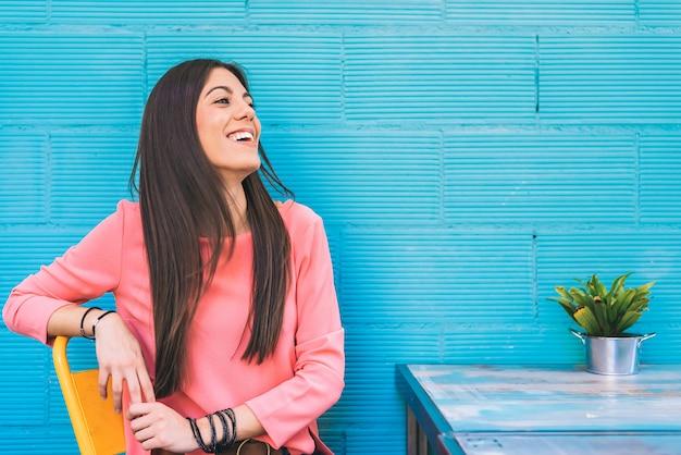 Disposizione dei posti a sedere felice della giovane donna in un ristorante