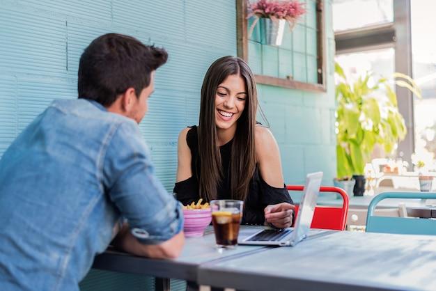 Disposizione dei posti a sedere felice delle giovani coppie in un ristorante con un computer portatile