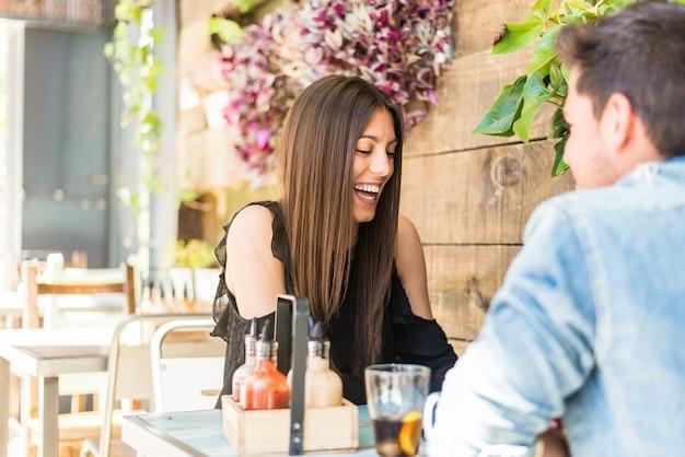 Disposizione dei posti a sedere felice delle giovani coppie in un ristorante