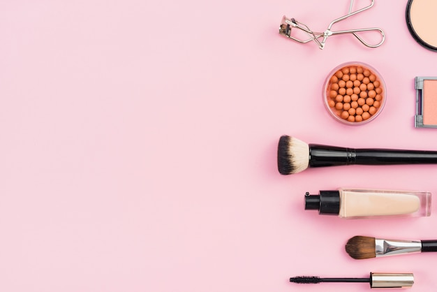 Disposizione dei prodotti di trucco su sfondo rosa