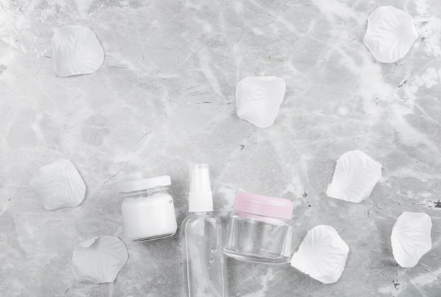 Disposizione dei prodotti per la cura del viso distesi su fondo in marmo