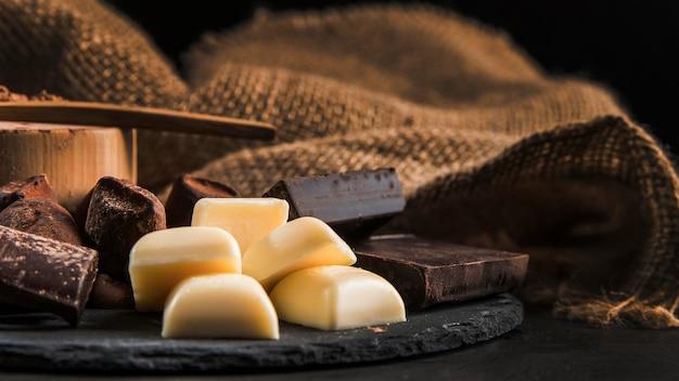 Disposizione del cioccolato zuccherato sul primo piano del bordo scuro