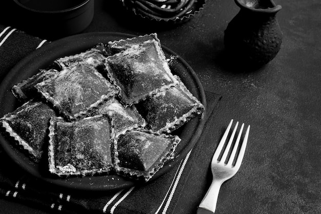 Disposizione del delizioso cibo nero sul piatto scuro e sul tavolo