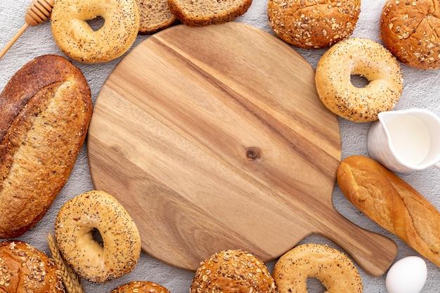 Disposizione del pane che circonda una tavola di legno dello spazio della copia