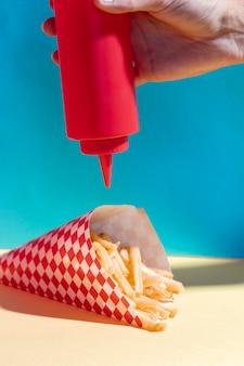 Disposizione del primo piano con persona che versa ketchup