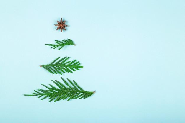 Disposizione dell'albero di natale dei rami verdi sul blu