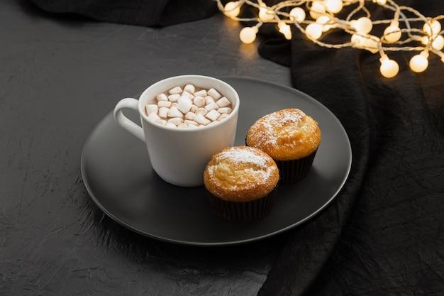Disposizione dell'angolo alto con la bevanda e i muffin della caramella gommosa e molle