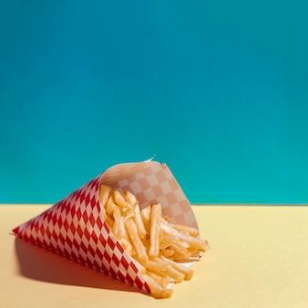 Disposizione dell'angolo alto con le patate fritte deliziose sulla tavola gialla