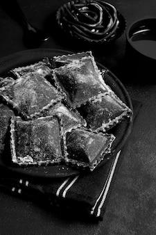 Disposizione dell'angolo alto di alimento delizioso nero sul piatto e sulla tavola scuri