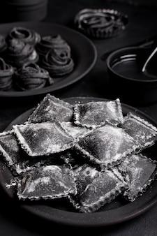Disposizione dell'angolo alto di alimento delizioso nero sulla tavola scura